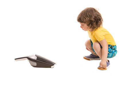 toddler boy: Toddler boy being amazed by hand-held vacuum cleaner isolated on white background