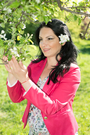 admire: Happy woman in nature admire apple flower in spring landscape Stock Photo