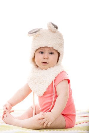 baby sitting: Beautiful baby girl in fluffy bunny hat  sitting on blanket Stock Photo