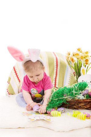 Baby girl sitting on blanket and playing with Easter eggs against white background photo