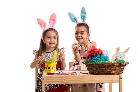 wry: Happy two girls decorating Easter eggs isolated on white background