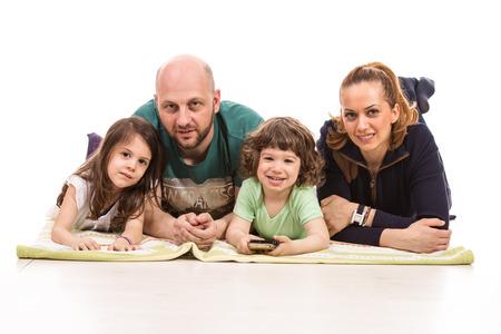 fondo blanco: Feliz familia de cuatro miembros que se acuesta y que sonríe a la cámara Foto de archivo