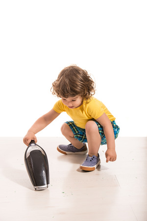 handheld: Toddler boy cleaning house with hand-held vacuum cleaner