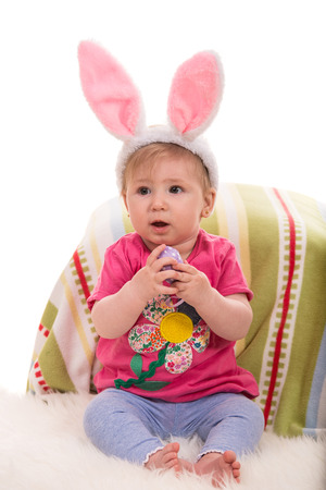 lilla: Beautiful baby girl with bunny ears holding Easter egg Stock Photo