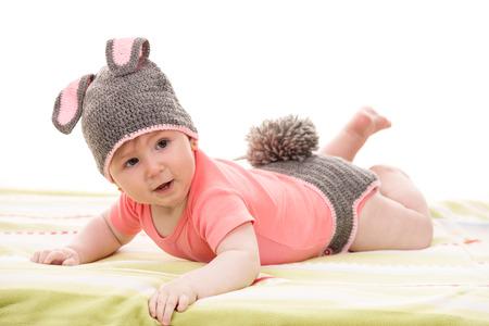 niños sentados: Pequeño bebé en traje de conejito croched tendido y mirando a otro lado