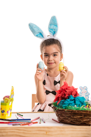 creative egg painting: Cute girl at table showing colorful Easter eggs isolated on white background Stock Photo