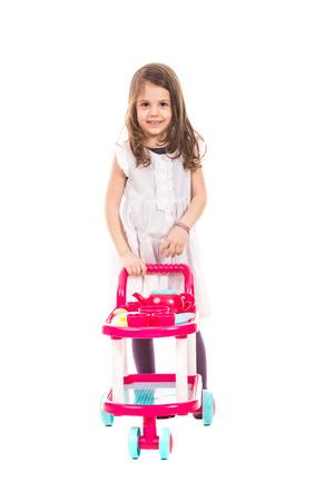 niño empujando: Muchacha sonriente caminando y empujando el cochecito de juguete aislado en el fondo blanco Foto de archivo