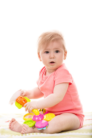 surprised baby: Surprised baby girl playing with  colorful flower toy