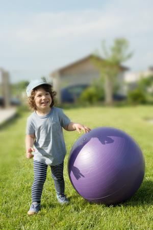 big ball: Little toddler boy having fun outside with big ball