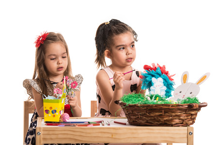 wry: Two girls painting Easter eggs and making decorations at table Stock Photo