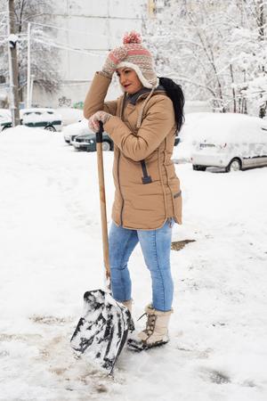 snow break: Working woman with snow shovel take a break