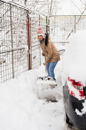 Woman shoveling snow around car  in a cold day