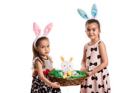 fluffy ears: Two girls holding Easter basket isolated on white background