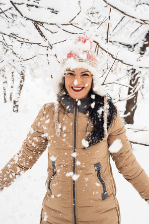 tossing: Cheerful woman  tossing snow in the park and having fun Stock Photo