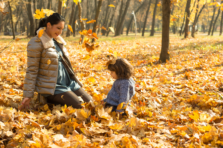 family outside: Happy mother and son playing with leaves in park and sitting down together