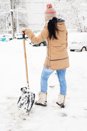 shoveling: Back of woman take a break from shoveling snow in parking Stock Photo
