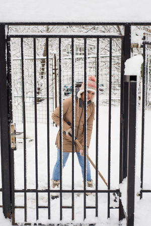 shoveling: Woman shoveling snow by fence and smiling