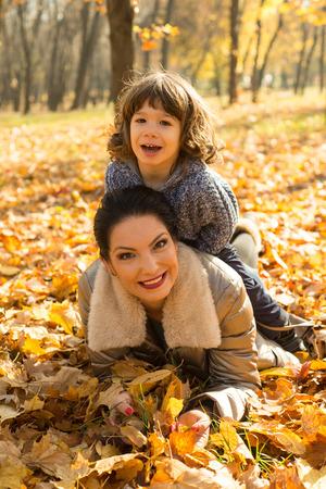mama e hijo: Hijo sentado en la parte superior de su madre y se divierten juntos en el parque del otoño