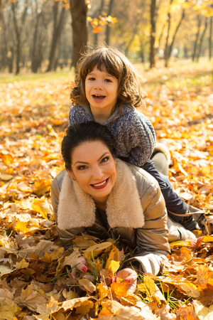 mom son: Son sitting on top her mother and having fun together in autumn park