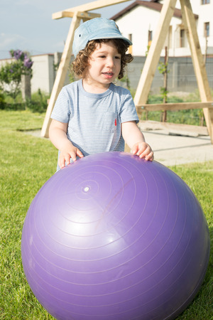 big ball: Toddler boy playing with big ball outside in garden