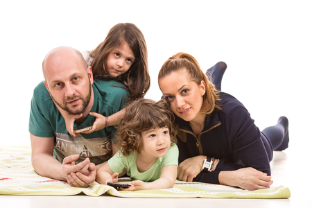 Happy family of mother,father and two kids laying on floor photo