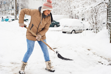 Happy woman showveling snow in parking around house Stock Photo