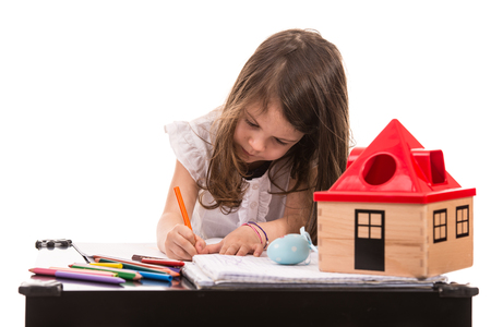 Little girl sitting at table and drawing with colorful pencils photo