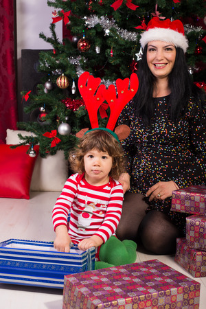 baby open present: Cheerful mother and son at Christmas celebrating and opening presents Stock Photo