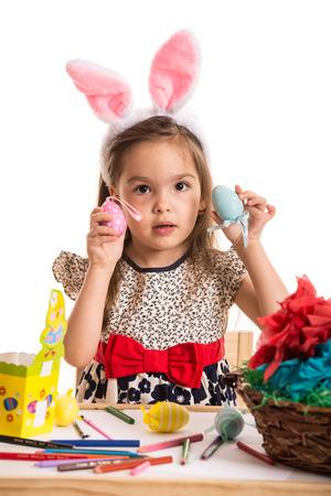 niñas pequeñas: Las niñas que muestran los huevos de Pascua coloridos delante de fondo blanco