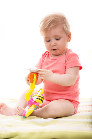 girl holding flower: Baby girl holding flower toy and playing on blanket home