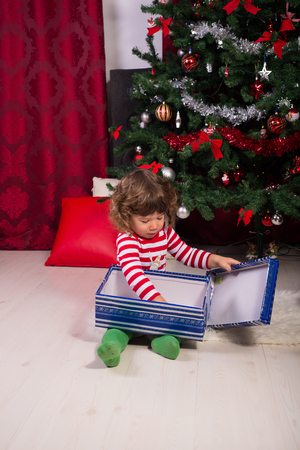 christmas present box: Toddler opening and playing with Christmas present box Stock Photo