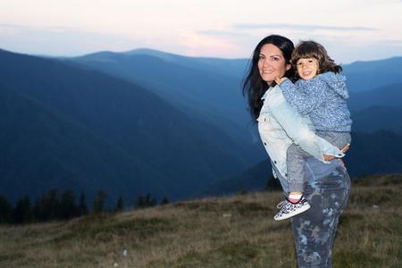 Glückliche Mutter und Sohn Huckepack in den moutains bei Sonnenuntergang