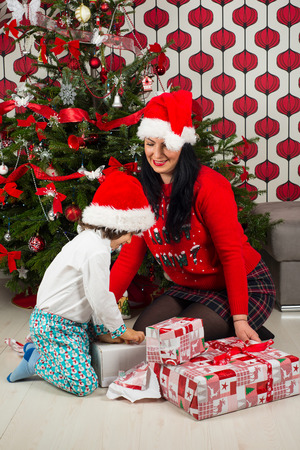 Little boy with mother opening Xmas gifts in front of Chritmas tree Stock Photo