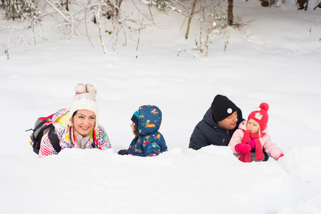 Happy family of four members lying down in snow in a row photo