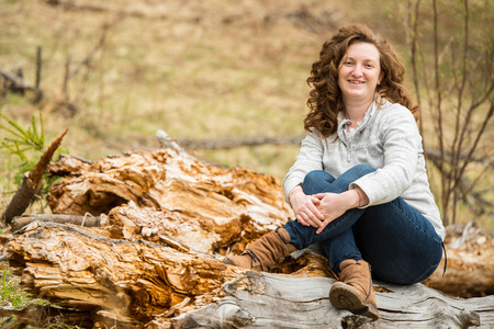 Smiling curly  woman sitting with crossed legs on a bark tree photo