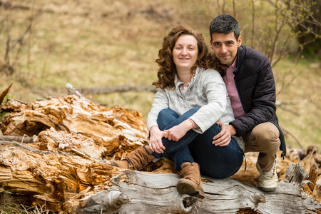 Cheerful middle aged couple  sitting on a bark tree outdoor photo