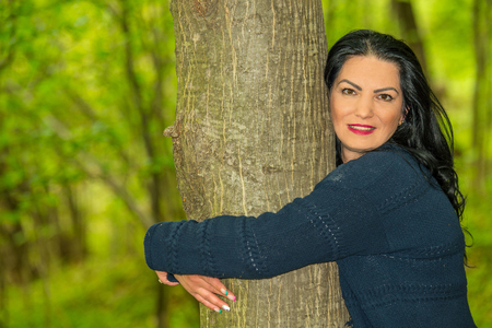 Cose up of smiling woman embracing a tree in forest Stock Photo