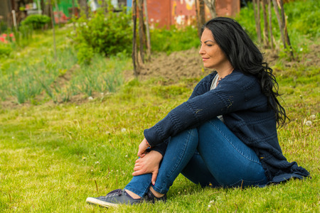 Thoughtful woman stting on grass in garden