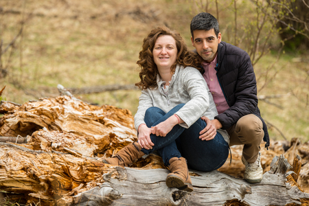 Cheerful couple sitting on a trunk  tree  and posing together photo