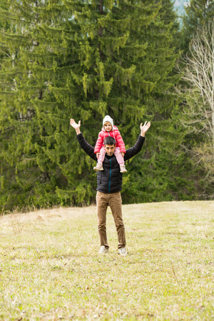 Cheerful dad and daughter having a walk in nature photo