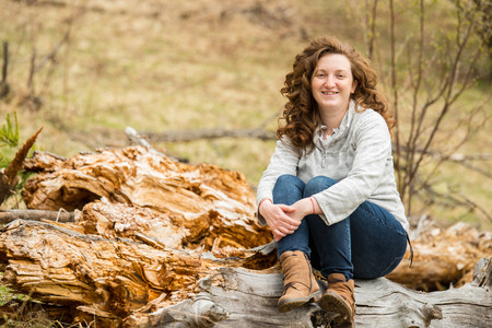Happy curly hair woman sitting on trunk tree in nature photo