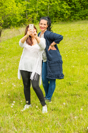 Friends women making selfie with their smartphone in nature photo