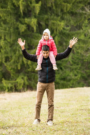 Happy father and daughter walking in nature at mountain photo
