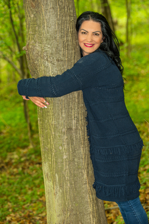 Happy woman embrace a tree in the forest