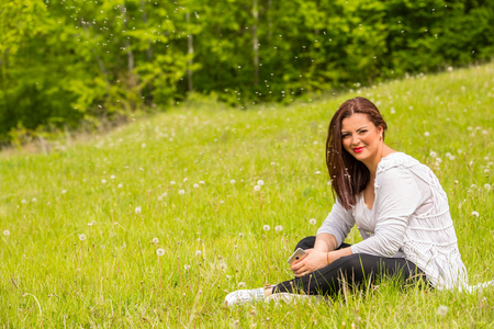 Woman with dandelions seeds around her in nature photo