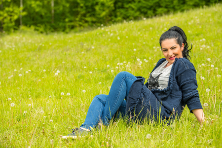 Attractive woman sitting on green grass in nature photo