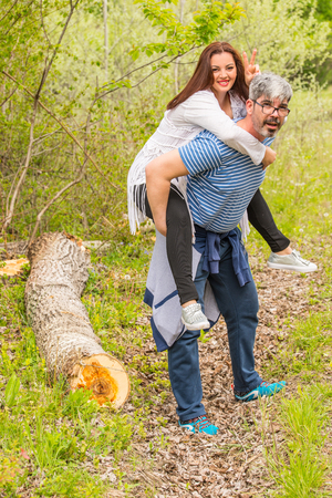 Man and woman having fun  and husband giving piggyback to his wife