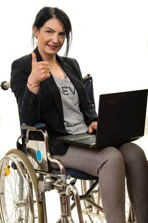 Successful business woman in wheel chair working on laptop, isolated on white background