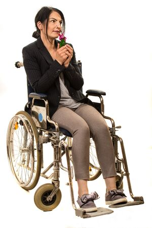 Woman in wheelchair smelling a flower isolated on white background