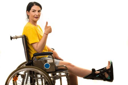 Smiling woman in wheelchair with feet orthosis giving thumb up isolated on white background